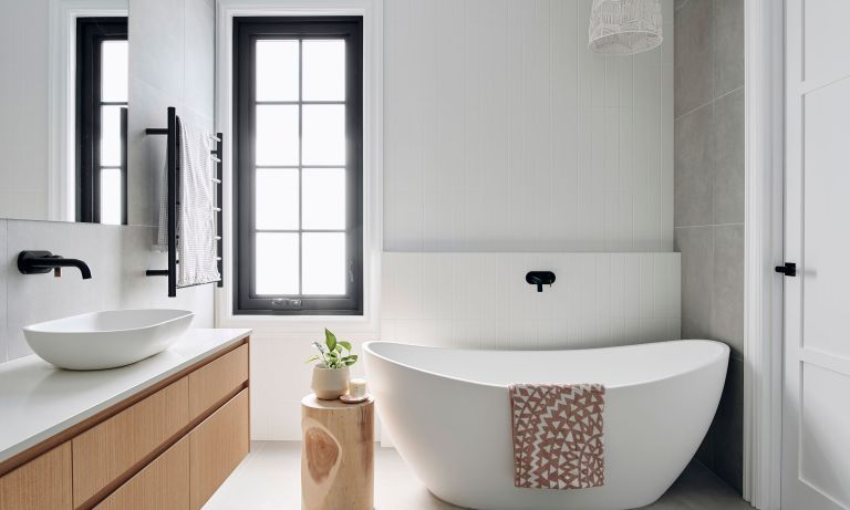 White bathroom with matching tub, wooden cabinets and crittal style/black painted window frame