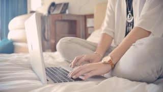 Woman typing on Apple Mac in hotel bed