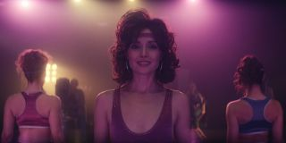Rose Byrne with a bouncy hairdo and silver hoop earrings, wearing a sequinned purple leotard, as Sheila Rubin stands in a brightly lit aerobics studio to shoot a fitness video
