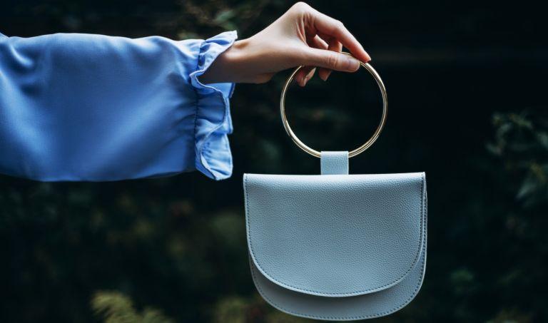 woman holding a blue handbag