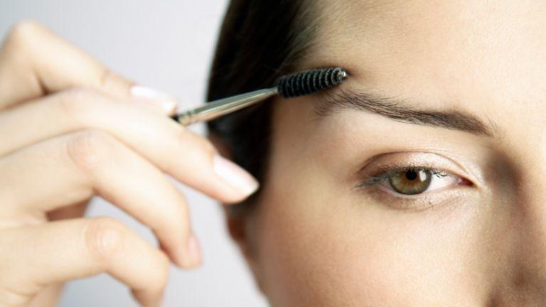 Woman Brushing Eyebrows - stock photo