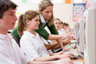 Female teacher points to monitor as students work at their computers