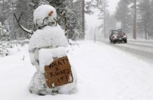 A snowman holds a sign along the race route on Highway 89 after stage one of the 2011 Amgen Tour of California from South Lake Tahoe to North Lake Tahoe was cancelled