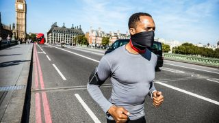 A man wearing a gaiter to cover his mouth and nose runs in central London.