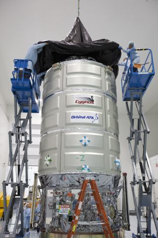 In the Space Station Processing Facility high bay at NASA's Kennedy Space Center in Florida, a crane is used to lower a protective covering around the Cygnus pressurized cargo module.