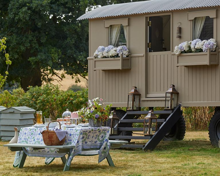 An example of garden picnic ideas showing a shepherd's hut with floral window boxes next to an alfresco dining table