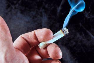 Hand holding smoking marijuana joint on black background with smoke