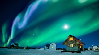 The northern lights glow green and purple above Great Slave Lake in the Northwest Territories of Canada.