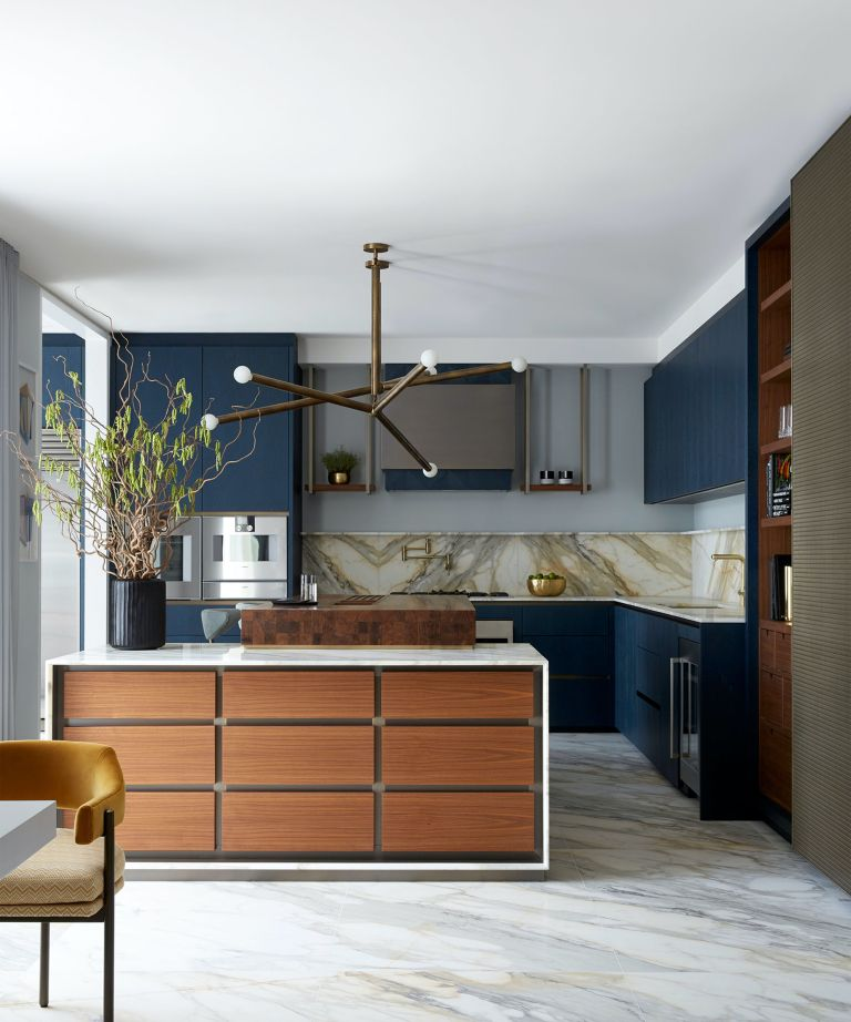 Kitchen island lighting ideas in the form of a brass statement pendant light in a blue, wood and marble kitchen scheme.