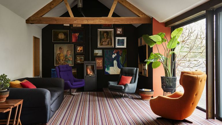 Wood burner in living room with various velvet chairs in purple and orange, striped carpeted floor and framed wall prints