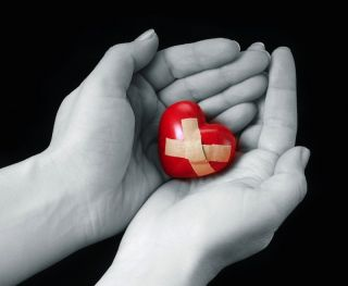 A woman holds an image of a heart in her hands.