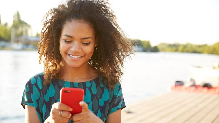 Woman using a smartphone looking happy