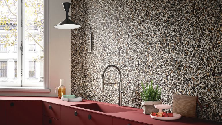 terrazzo tiles backsplash in a kitchen with matte red cabinets and chrome tap