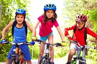 Three children ride their bikes together.