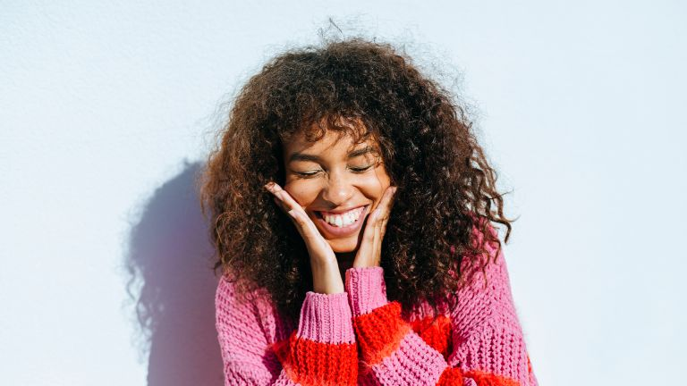 Portrait of laughing young woman with curly hair against white wall - stock photo