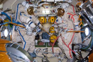 Two Russian Orlan spacesuits sit empty on the International Space Station ahead of a spacewalk in 2014. Space Adventures and Roscosmos have booked a private spacewalk for one of two space tourists flying to the station in 2023.