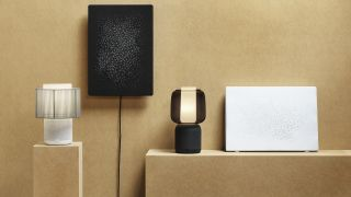 The IKEA Symfonisk smart table lamp on a shelf next to other Ikea smart home kit. The shelf and wall behind it are beige.