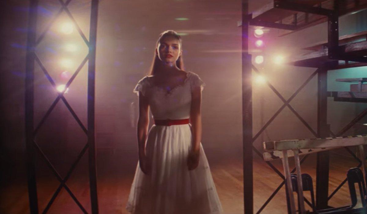 Rachel Zegler walking behind the bleachers in West Side Story.