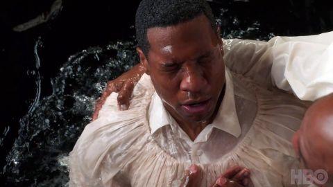 Atticus (Jonathan Majors) is baptized.