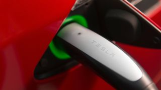 Close up of a charger plugged into the charging port of a Tesla car