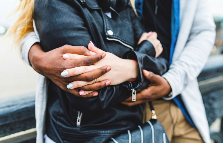 multiracial couple, embracing and holding hands - stock photo