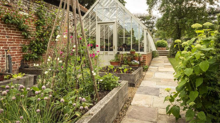 upcycling ideas showing raised beds with reclaimed sleepers in front of a greenhouse