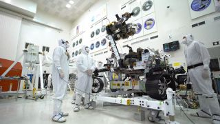 """Engineers decked out in protective """"bunny suits"""" inspect the Perseverance rover in a clean room in 2019, before the spacecraft launched to Mars."""
