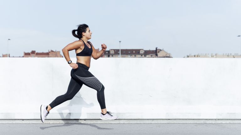 woman running outside by white wall