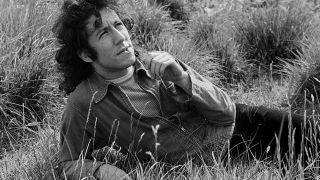 Peter Green relaxed in a field, chewing grass