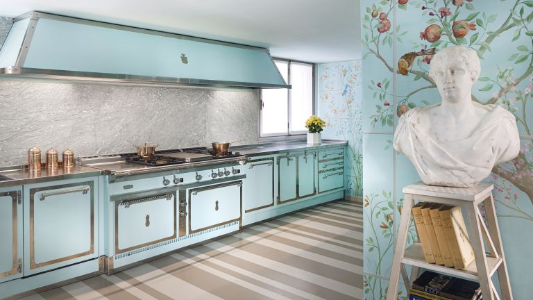 A kitchen with turquoise cooking range and turquoise tiled walls hand-painted with muralistic motifs of birds, animals, fruit trees and flowers