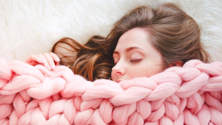 woman under thick knitted blanket