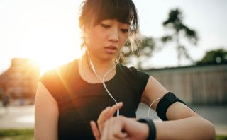 Woman looks at wearable device while running