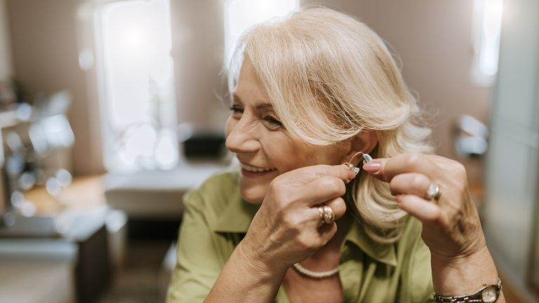 Woman putting in hearing aid