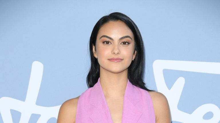 Camila Mendes wearing pink in front of pale blue wall