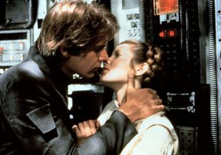Harrison Ford and Carrie Fisher share a kiss aboard his ship the Millennium Falcon