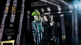Stars Alex Brightman (left) and Sophia Anne Caruso stand illuminated by a mixture of traditional stage lighting and laser projection.