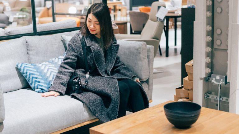 Young woman at furniture store choosing sofa - stock photo