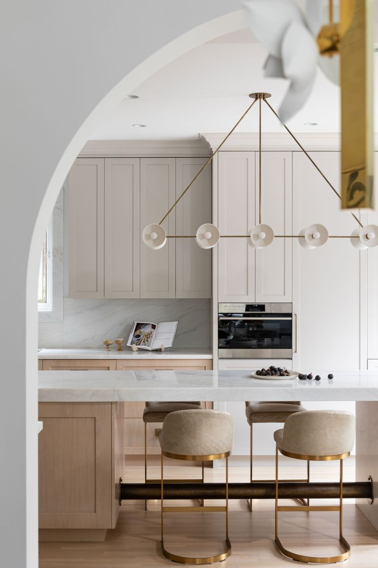 An example of how to make a small kitchen look bigger showing a kitchen with cream units and a glamorous light fitting