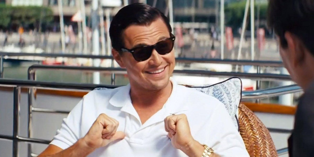 Leonardo DiCaprio points to himself with thumbs as he smiles in The Wolf of Wall Street.