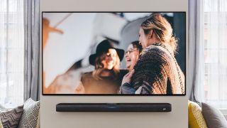 the polk react soundbar mounted beneath a tv