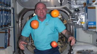 Astronaut and Oranges Float in Expedition 30 Spacecraft
