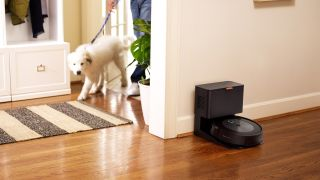 The iRobot Roomba J7+ on its charging station in a hallway while a man with a dog enters the room