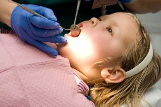 Adorable little blond girl getting her teeth checked at the dentist