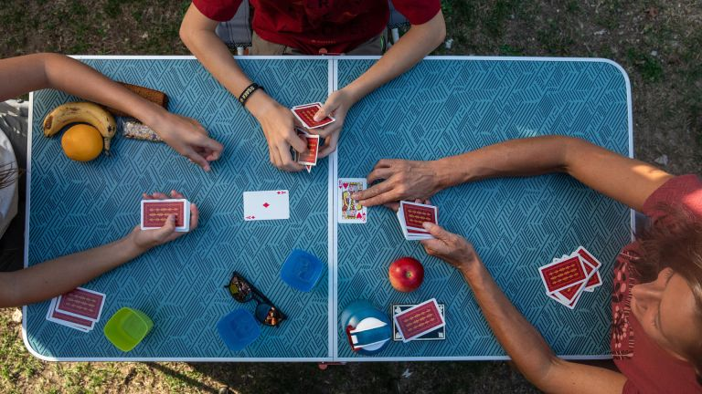 best camping table: people playing cards on Decathlon Quecha Folding Camping Table