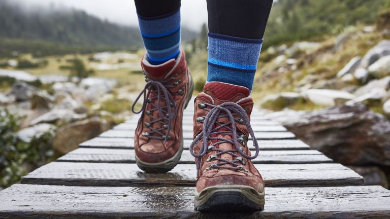 person walking along wooden bridge wearing hiking boots