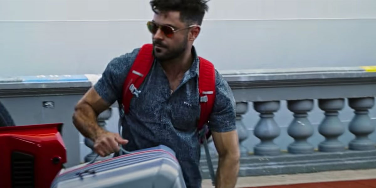 Efron lugging suitcase in Down to Earth Season 1 on Netflix