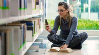 Young woman texts while sitting on library floor next to book shelves.