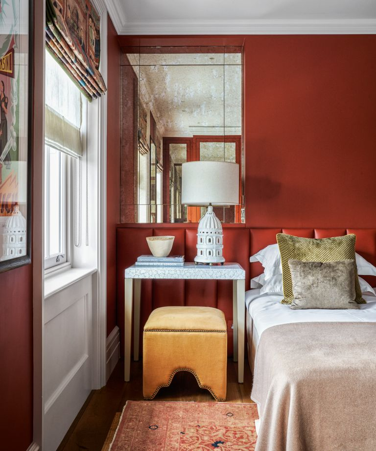 A colorful bedroom with deep red walls, yellow stool and neutral bedding
