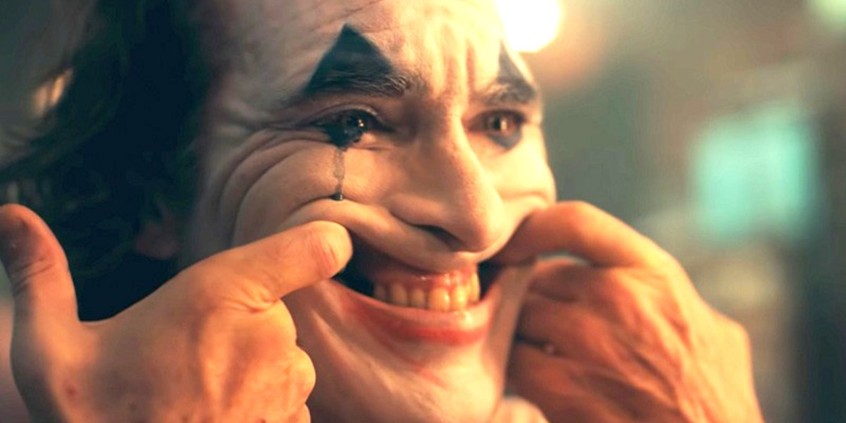 Joaquin Phoenix Joker movie stretching mouth into smile