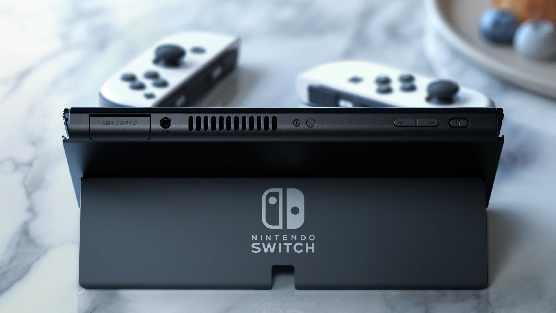 Nintendo Switch OLED on a marble table in tabletop mode